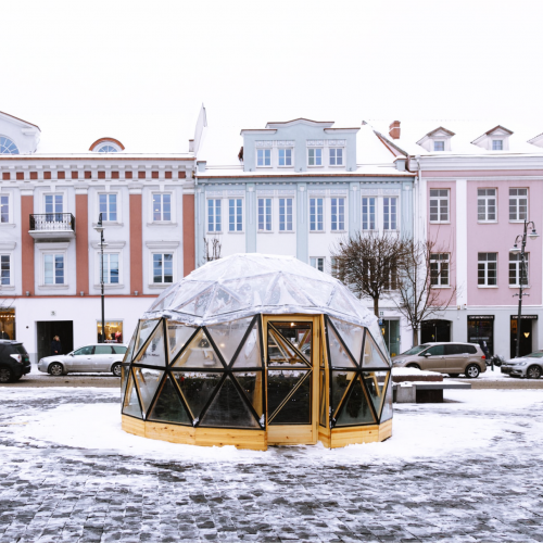 Small decorated wooden Christmas Market house covered with snow in Vilnius Town Hall square